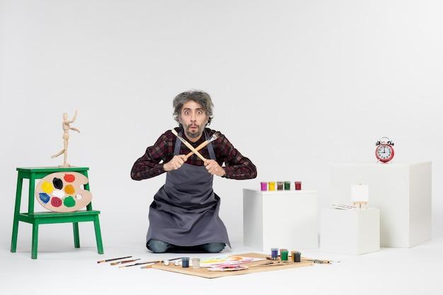 흰색 배경에 페인트와 페인트 브러시가 있는 방 안에 있는 전면 보기 남성 화가 그림 예술가는 직업 예술을 그립니다.