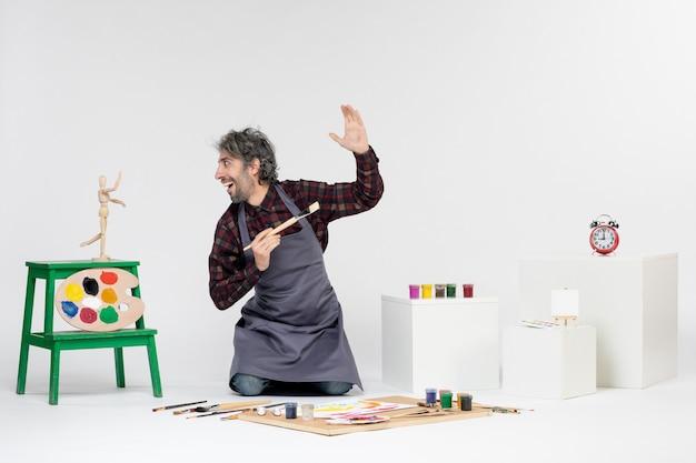 Vista frontale pittore maschio all'interno della stanza con vernici e pennelli per disegnare su sfondo bianco arte artista pittura uomo immagini a colori disegnare