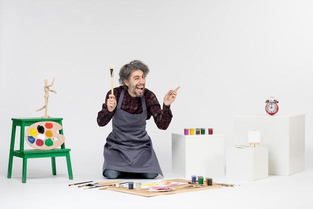 Vista frontale pittore maschio all'interno della stanza con vernici e pennelli per disegnare su sfondo bianco arte disegnare uomo artista pittura immagine a colori