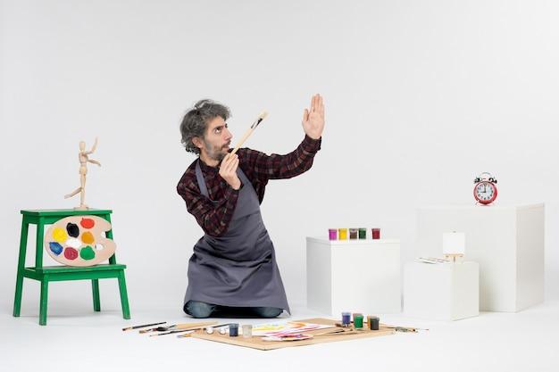 Vista frontale pittore maschio all'interno della stanza con vernici e pennelli per disegnare su sfondo bianco arte disegnare l'immagine della pittura dell'artista dell'uomo