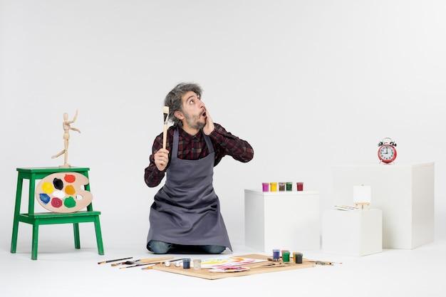 Vista frontale pittore maschio all'interno della stanza con vernici e pennelli per disegnare su sfondo bianco arte disegnare un uomo che dipinge un'immagine a colori