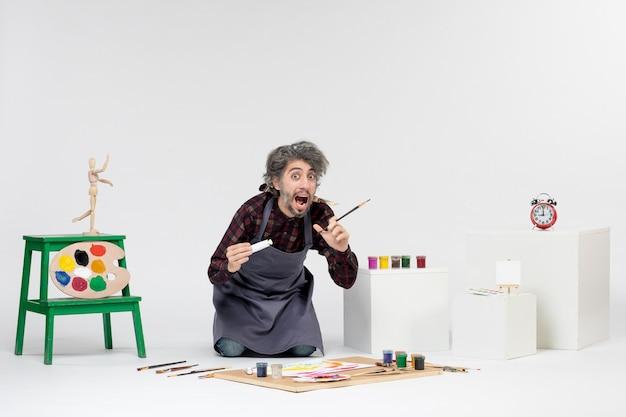 Vista frontale pittore maschio all'interno della stanza con vernici e pennelli per disegnare su sfondo bianco disegnare l'uomo artista pittura arte immagine a colori
