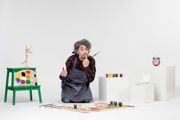 Vista frontale pittore maschio all'interno della stanza con vernici e pennelli per disegnare su sfondo bianco disegnare artista uomo che dipinge immagini a colori d'arte