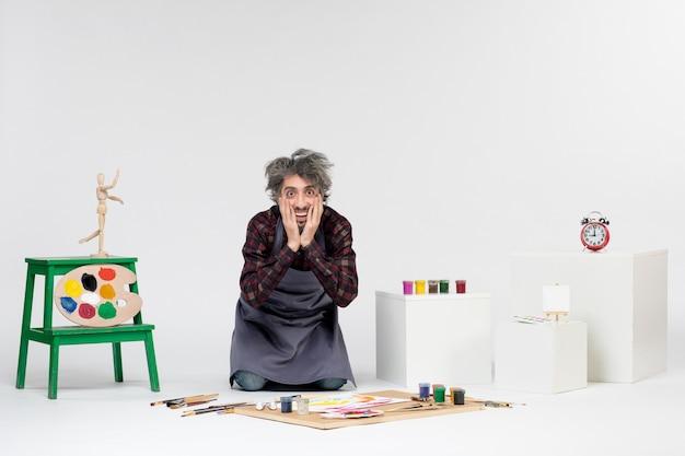 Vista frontale pittore maschio all'interno della stanza con vernici e pennelli per disegnare su sfondo bianco artista uomo che dipinge immagini a colori d'arte
