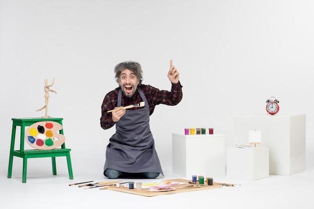 Vista frontale pittore maschio all'interno della stanza con vernici e pennelli per disegnare su sfondo bianco uomo colore arte pittura immagini artista disegnare