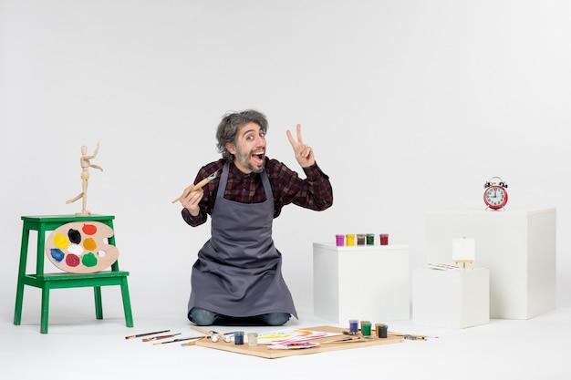 Vista frontale pittore maschio all'interno della stanza con vernici e pennelli su sfondo bianco arte immagine a colori disegnare lavoro artista