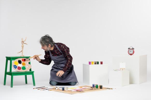 Vista frontale pittore maschio all'interno della stanza con vernici e pennelli su sfondo bianco colori pittura immagine disegnare lavoro artistico artista