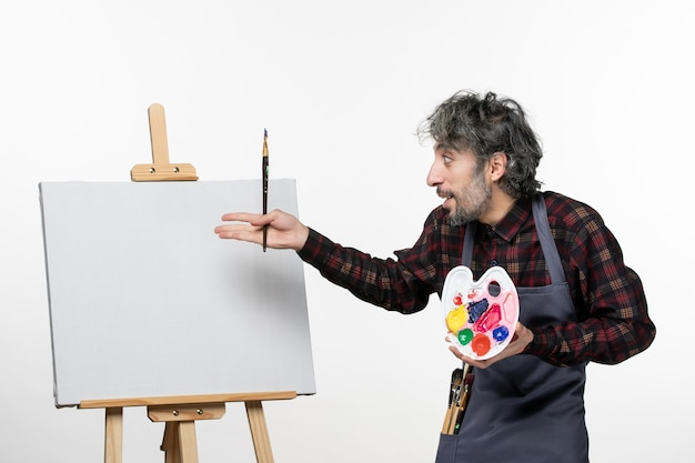 Front view male painter preparing to draw with paints and paint brush on a white wall