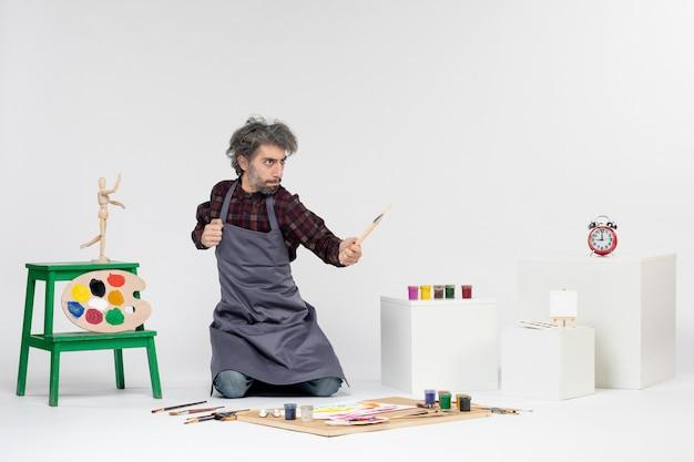Vista frontale pittore maschio che si prepara a disegnare con vernici su sfondo bianco artista artistico disegno pittura colore
