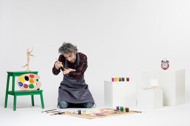 Vista frontale pittore maschio che si prepara a disegnare con le vernici su uno sfondo bianco immagine artistica artista disegno pittura colore