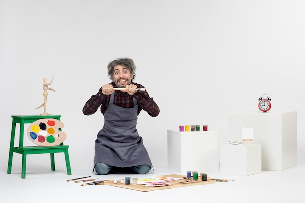 Vista frontale pittore maschio che si prepara a disegnare con vernici su sfondo bianco immagine artistica disegno pittura colore