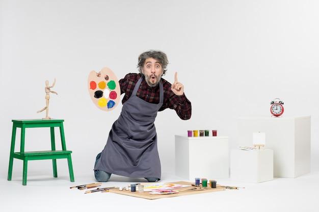 Vista frontale pittore maschio che si prepara a disegnare con le vernici sullo sfondo bianco disegno a colori artista pittura arte immagine uomo