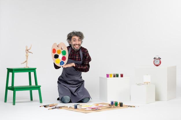 Vista frontale pittore maschio che si prepara a disegnare con vernici su sfondo bianco colore uomo disegno artista pittura immagine artistica