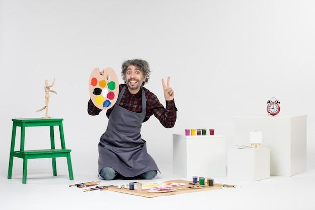 Vista frontale pittore maschio che si prepara a disegnare con vernici su sfondo bianco colore uomo immagine artista pittura arte