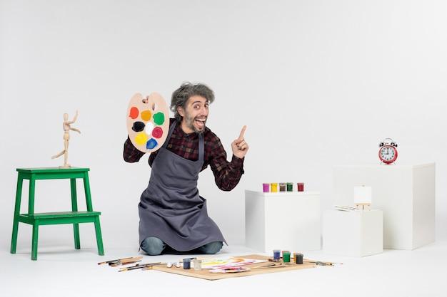 Vista frontale pittore maschio che si prepara a disegnare con vernici su sfondo bianco colore uomo immagine disegno artista pittura arte