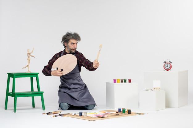 Vista frontale pittore maschio che si prepara a disegnare con le vernici sullo sfondo bianco uomo arte immagine artista disegno pittura colore