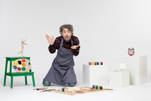 Vista frontale pittore maschio che si prepara a disegnare con le vernici sullo sfondo bianco uomo che disegna artista pittura arte immagine a colori