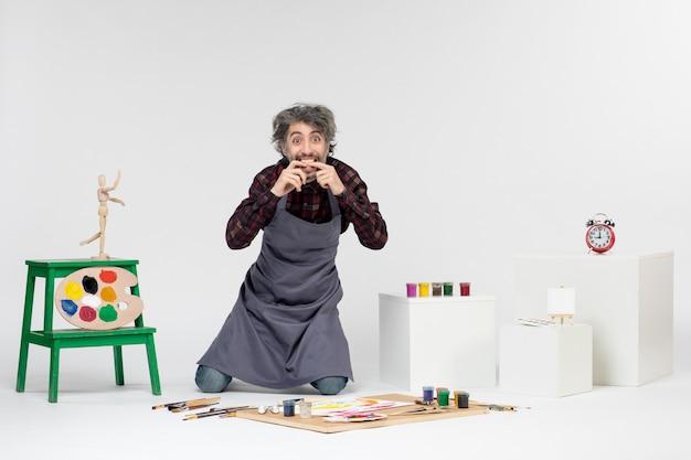 Vista frontale pittore maschio che si prepara a disegnare con le vernici sulla scrivania bianca uomo che disegna artista pittura arte immagine a colori