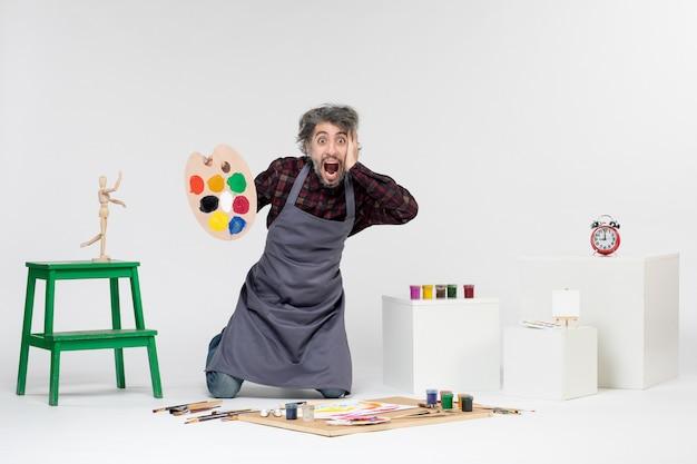 Вид спереди художник-мужчина готовится рисовать красками на белом фоне, цветной рисунок, художник, художественная фотография, человек