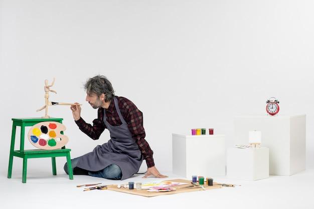 Vista frontale pittore maschio seduto con vernici e nappe per disegnare sullo sfondo bianco arte disegno immagine artista pittura a colori