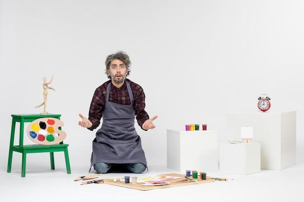 Vista frontale pittore maschio seduto con vernici e nappe per disegnare su sfondo bianco arte disegno immagine artista colori pittura