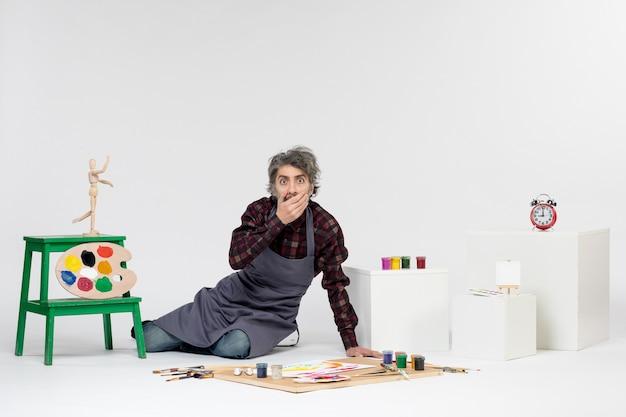 Vista frontale pittore maschio seduto con vernici e nappe per disegnare su sfondo bianco disegno a colori immagine artistica pittura dell'artista