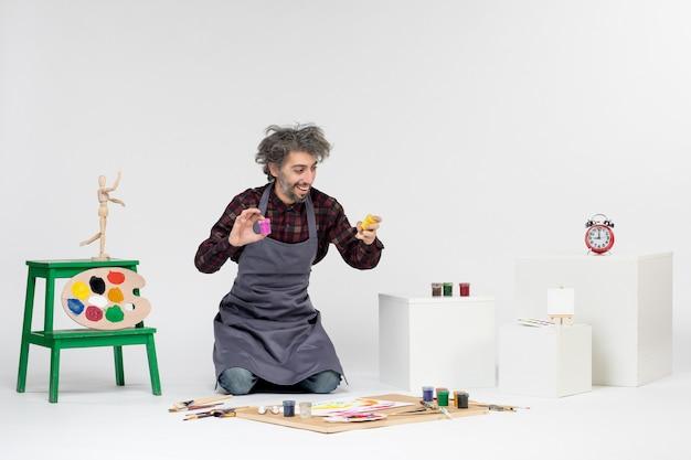 Vista frontale pittore maschio seduto con vernici e nappe per disegnare su sfondo bianco disegno a colori immagine artista pittura