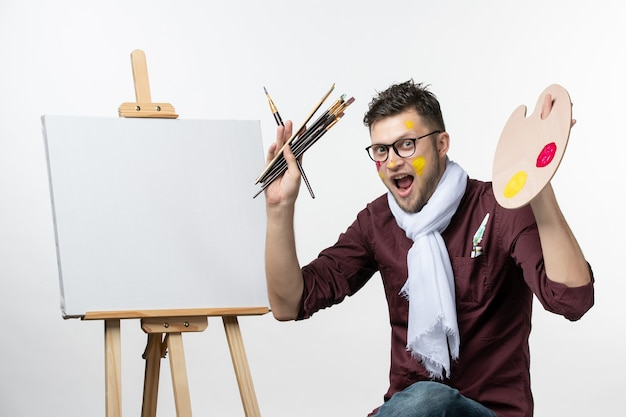 Front view male painter trying to draw on easel holding paint brushes and paints on white wall