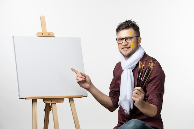 Front view male painter trying to draw on easel holding paint brushes on white wall