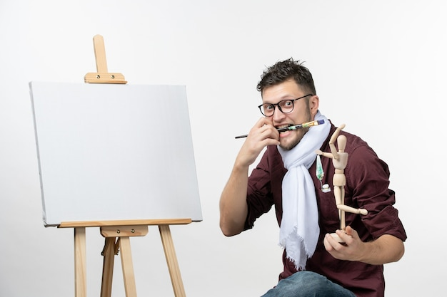 Front view male painter trying to draw on easel on the white wall