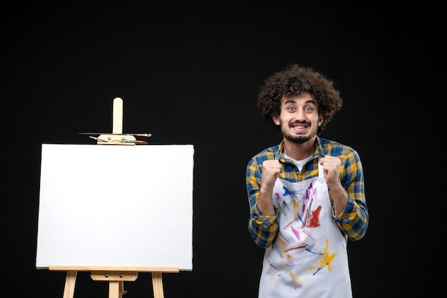 Front view male painter with easel holding toy human figure on black wall