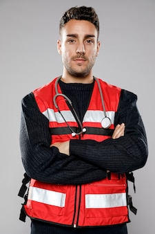 Front view of male paramedic with crossed arms