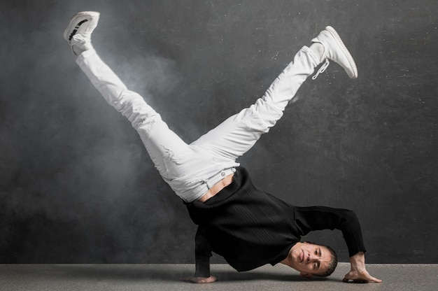 Front view of male performer in jeans and sneakers posing while holding legs up