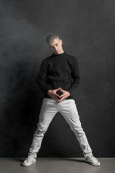 Vista frontale dell'esecutore maschio che posa in jeans e scarpe da tennis