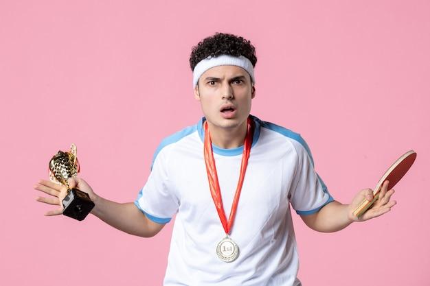 Вид спереди мужской игрок в спортивной одежде с золотым кубком и медалью