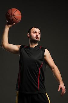 Vista frontale della pallacanestro di lancio del giocatore maschio