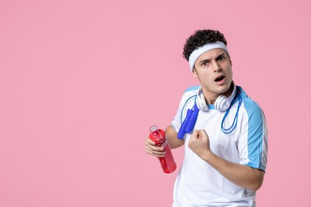 Вид спереди мужской игрок со скакалкой, держащий бутылку воды