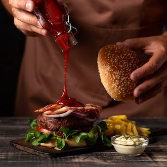正面の男性がハンバーガーにソースを入れて