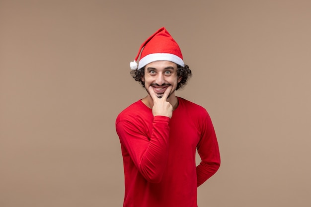 Front view male in red smiling on brown background holiday emotion christmas