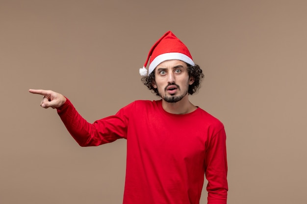Front view male in red with nervous expression on brown background holiday emotion christmas