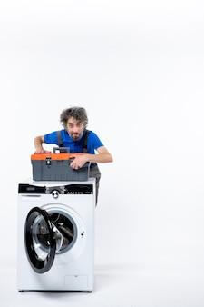 Вид спереди мужской ремонтник, закрывающий сумку с инструментами за стиральной машиной на белом пространстве