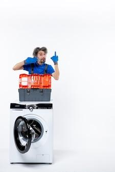 흰색 공간에 세탁기 뒤에 그의 배수 장갑을 보여주는 전면 보기 남성 수리공