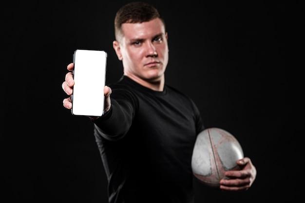 Vista frontale del giocatore di rugby maschile che tiene palla e smartphone