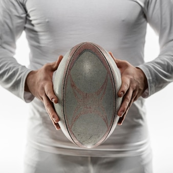 Front view of male rugby player holding ball with both hands