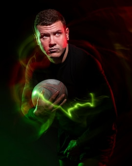 Front view of male rugby player holding ball with color effect