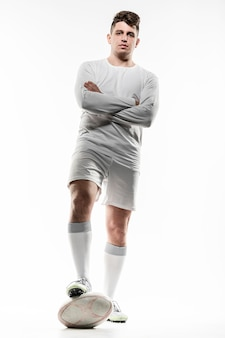 Front view of male rugby player posing with ball and arms crossed