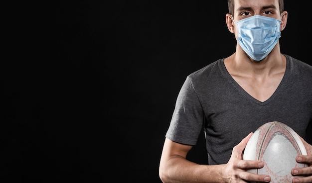 Vista frontale del giocatore di rugby maschile con maschera medica e copia spazio
