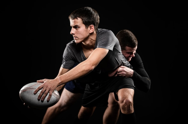 Front view of male rugby players with ball