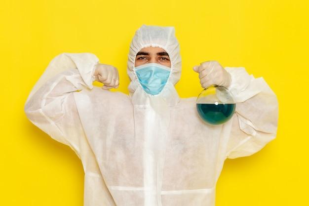 黄色の表面で曲がる青い溶液とフラスコを保持している特別な防護服の正面図男性科学者