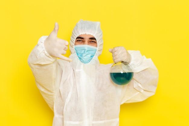 黄色の机の上でポーズをとって青い溶液とフラスコを保持している特別な防護服の正面図男性科学者